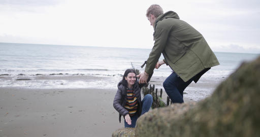 Boyfriend helping girlfriend climb a rock Live Action