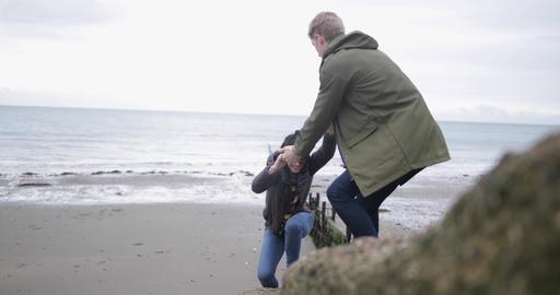 Boyfriend helping girlfriend climb a rock Stock Video Footage