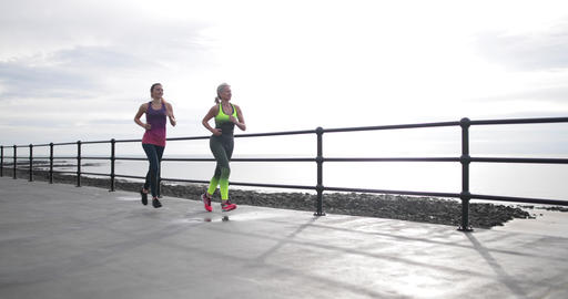 Active senior woman running with younger woman Footage