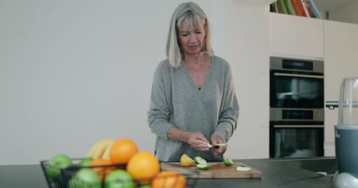 Senior woman cutting fruit for a smoothie Archivo