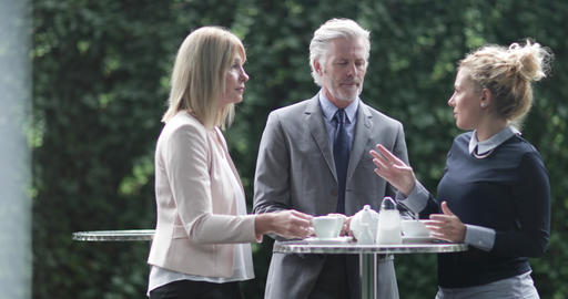 Colleagues talking at an outdoor coffee reception Live Action