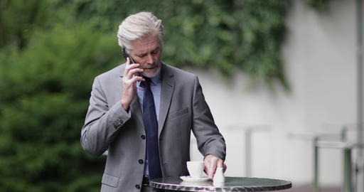 Senior business executive using a smartphone in a cafe outdoors Live Action