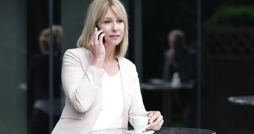 Female business executive using a smartphone in a cafe outdoors Footage