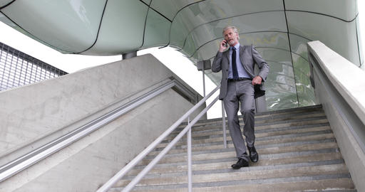 Senior businessman walking down stairs using smartphone outdoors Live Action