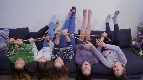 Five girls lying upside down on sofa and have fun Live Action
