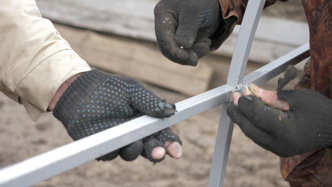 Male hand in gloves tightens bolt metal construction outdoor close up Footage
