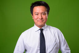 Mature Japanese businessman against green background フォト