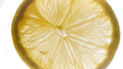 Slow motion footage of rotating backlit lemon slice Footage