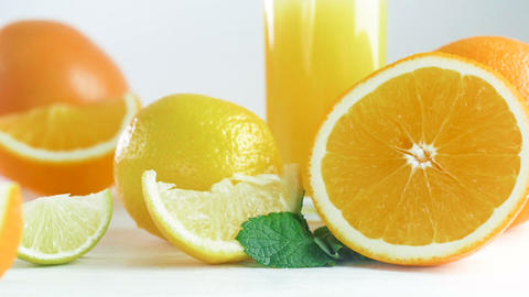 Closeup footage of oranges, limes, lemons and glass of orange juice on wooden Footage