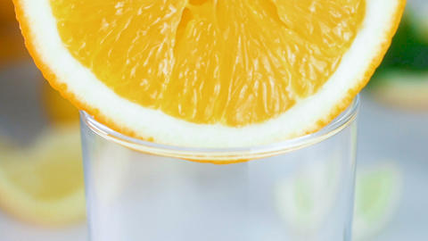 Macro slow motion footage of fresh juice flowing from orange slice in glass Footage