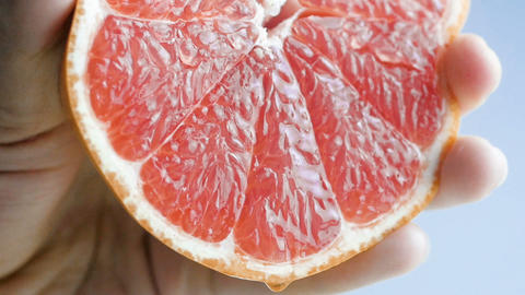 Closeup slow motion footage of hand squeezing fresh juicy grapefruit Footage