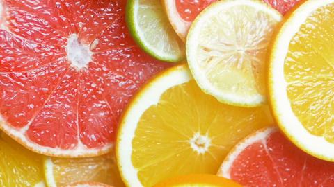 Slow motion video of assortment of fresh citrus fruits lying on table Footage