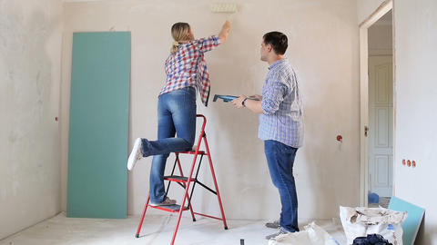 Cheerful young couple painting walls at their new home Footage
