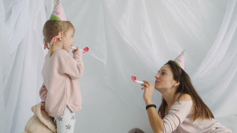 Little blondy girl and her mother blows festive horns Footage