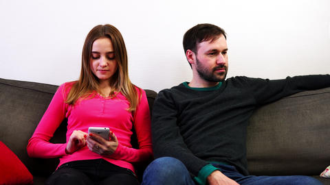 Man and woman sitting on sofa, woman look in smartphone, man turned away Footage