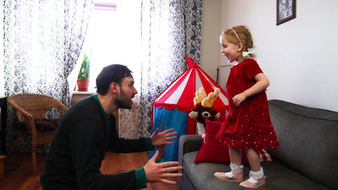 A cute little girl jumps from the sofa into her father's hands in slow motion Footage