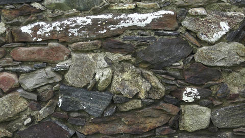 Fragment of a stone wall. The old wall is made of stone. Texture or background Footage