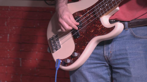 Bass player in jeans with white guitars Filmmaterial