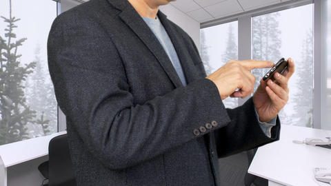 Businessman browsing vacation photos on smartphone in office in winter Live Action