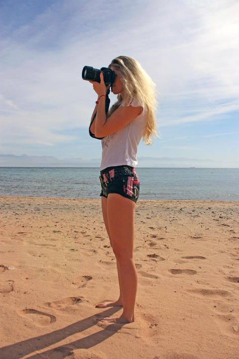 Blonde girl with camera shooting on the beach フォト