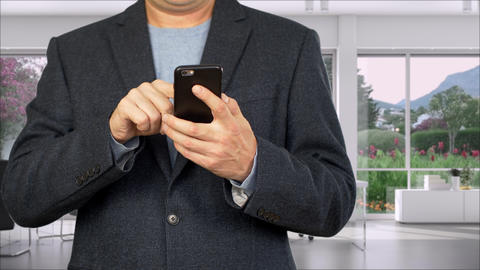 Business man in jacket typing on smartphone in office, partial view Footage