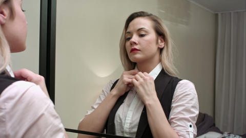Young businesswoman putting on white blouse in bedroom at home, prepearing to a Footage