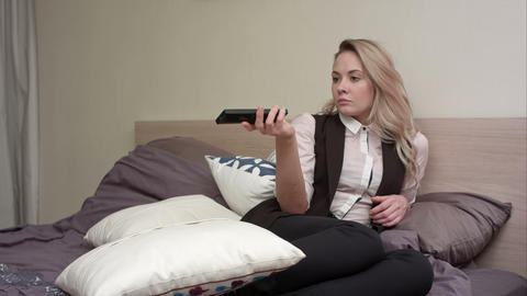 Young woman watching TV and switch channels in bed Footage