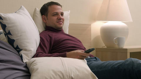 Mature handsome man relaxing in his hotel room looking for something to watch on Footage