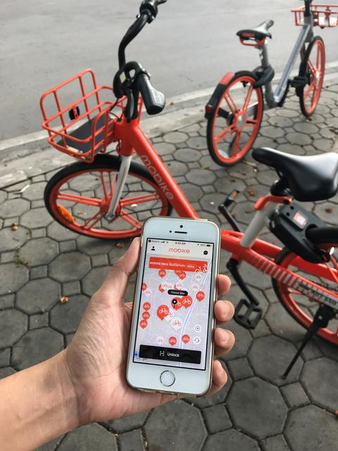 "using application on iPhone for ""mobike"" rental bicycle which parks on footpath フォト"