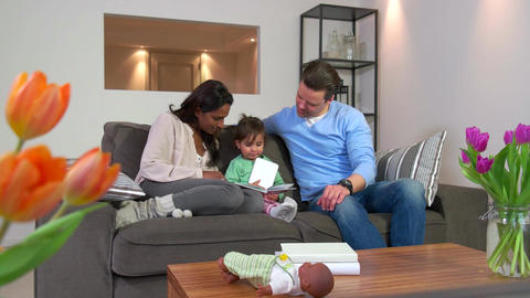 Multiethnic Couple Reading Book To Child Man Woman Daughter Baby stock footage