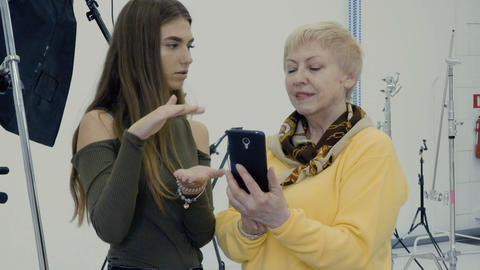 Two workers discuss made photos in photo studio Live Action