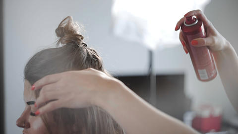 Hairdress sprays hair spray to the woman's hair, making the process of making Footage
