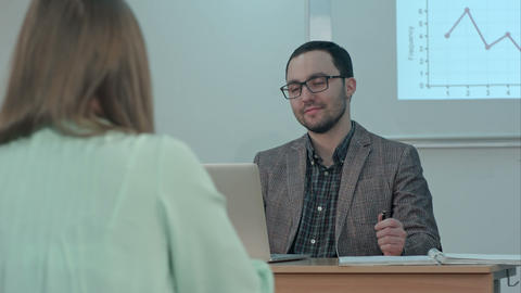 Handsome male teacher smiling and talking with students at the lesson Footage