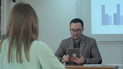 Teacher holding digital tablet in hands while teaching lessons in school Footage