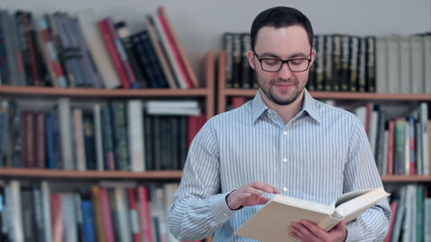 Young teacher holding book and looking at the camera Footage