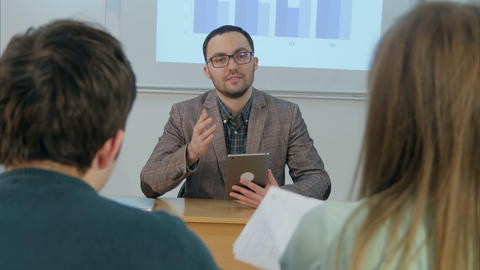 Male teacher holding a tablet sitting in front of class Footage