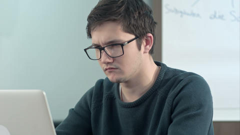 Young pensive student working on laptop at home office or library with serious Footage