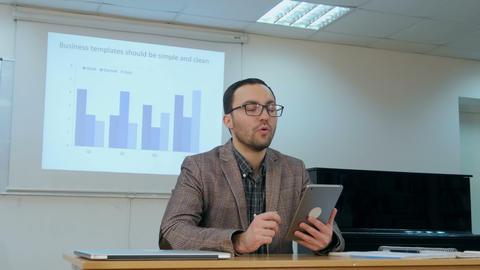 Teacher teaching kids on digital tablet in classroom at school Footage