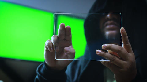 Hacker using clear tablet with green screen monitor background GIF
