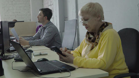 Retired woman use her phone in office during the work Footage