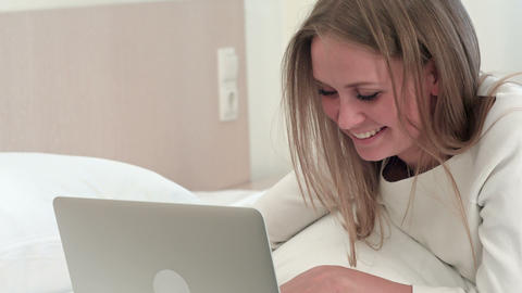 Smiling blonde woman using laptop as she lies on the bed at home or in a hotel Footage