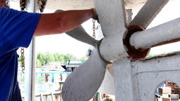 Worker paints metal of old rusty ship propeller at shipyard in port of Moscow Footage