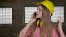 Young serious girl builder is talking on telephone, watching above Footage