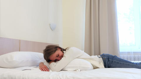 Relaxed pretty young woman sleeping on white bed in hotel room Footage