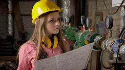Young serious girl builder is watching plan of building, thinking 영상물