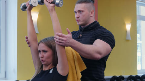 Personal instructor helping female client exercising with dumbbells in the gym Footage