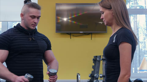 Personal trainer showing young woman how to use barbells in the gym Footage