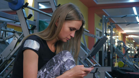 Young woman having a break in a gym and text messaging on her phone Footage