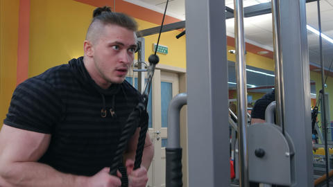 Muscular body builder working out at the gym on a cable machine Footage