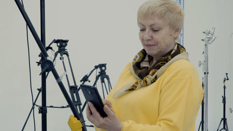 Mature woman make photo on her smartphone in photo studio Footage